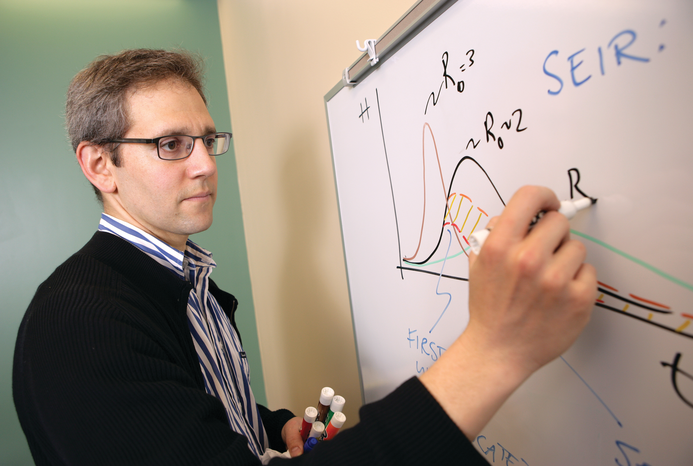Dr. Nathaniel Hupert writing on a white board.
