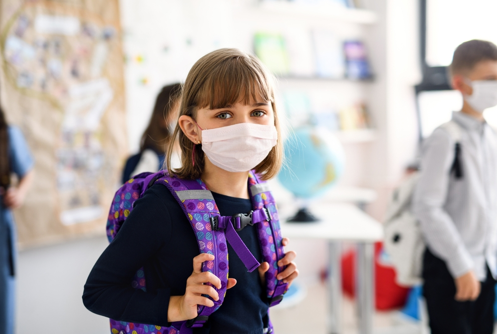 Image of young girl wearing face mask at school