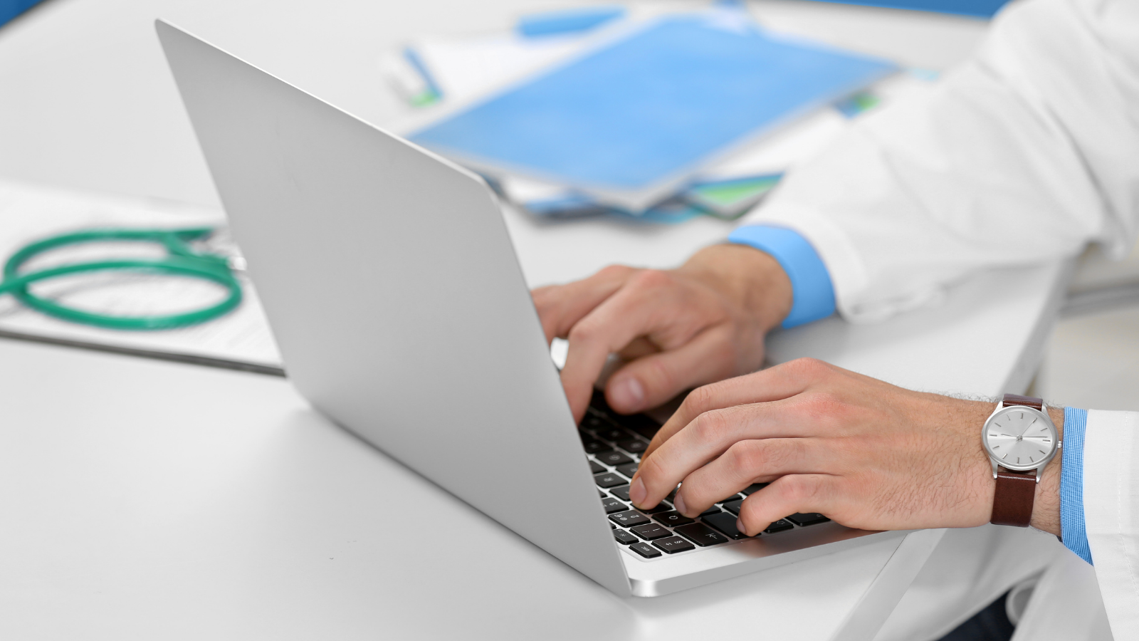 Physician typing on a computer