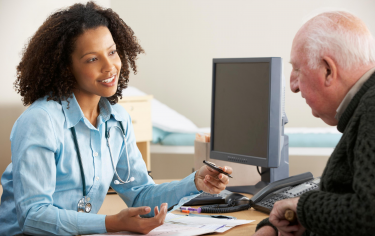 Photo of doctor speaking with patient at desk