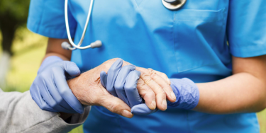 A nurse holding the hand of a nursing home resident.